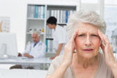 Senior patient suffering from headache with doctors at medical o — Stock Photo