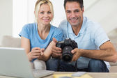 Couple with camera and laptop on sofa — Stock Photo