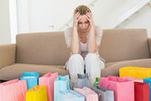 Regretful woman looking at many shopping bags on the couch — Stock Photo
