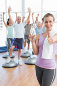 Woman gesturing thumbs up with people stretching hands fitness studio — Stock Photo