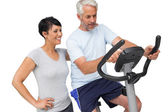 Happy woman looking at mature man on stationary bike — Stock Photo