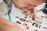 Closeup of a concentrate male artist looking at photos — Stock Photo