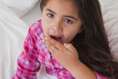 Young girl yawning in bed — Stock Photo