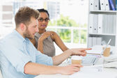 Casual business partners working together on laptop at desk — Stock Photo