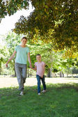 Happy mother and daughter walking at park — Foto Stock