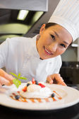 Closeup of a smiling chef garnishing food — Stock Photo