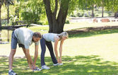 Active couple exercising in park — Stock Photo