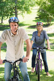 Couple riding cycles in park — Stock Photo