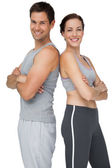 Portrait of a happy fit couple with hands crossed — Stockfoto