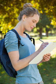 Beautiful young woman writing on clipboard at park — Foto Stock