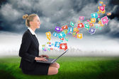 Businesswoman using laptop with app icons — Stock Photo