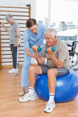 Therapist assisting senior man with dumbbells — Stock Photo