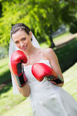 Bride with red boxing gloves in park — Stock Photo