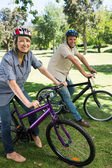Couple riding bicycles in parkland — Stock Photo