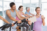 Trainer besides people working out at spinning class — Stock Photo