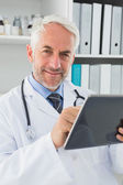 Male doctor using digital tablet at medical office — Stock Photo