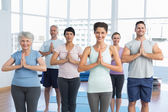 Sporty people with joined hands at fitness studio — Stock Photo