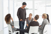 Rehab group listening to man standing up introducing himself — Stock Photo