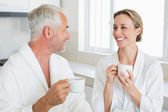 Smiling couple having coffee at breakfast in bathrobes — Stock Photo