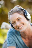 Beautiful young woman enjoying music in park — Stock Photo