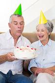 Senior couple sitting on couch celebrating a birthday — Stock Photo