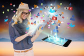Stylish blonde using tablet pc with app icons and smartphone — Stock Photo