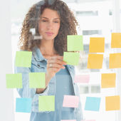 Focused designer looking at sticky notes on window — Stock Photo