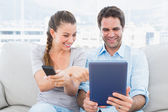 Happy couple sitting on the couch using tablet pc and watching tv — Stock Photo