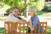 Happy couple relaxing on park bench — Stock Photo