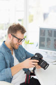 Handsome photographer holding his camera — Stock Photo