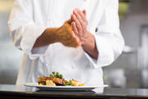 Mid section of a chef putting salt in kitchen — Stock Photo