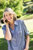 Parkta cep telefonu kullanan kadın — Stok fotoğraf