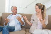 Angry couple sitting on couch arguing — Stock Photo