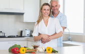 Affectionate couple preparing a vegetarian dinner together — Stock Photo