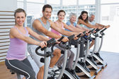 Happy people working out at spinning class — Stock Photo