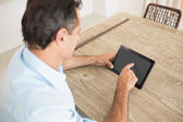 Concentrated man using digital table — Stock Photo