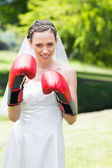 Bride wearing boxing gloves in garden — Stock Photo