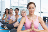 Class sitting with joined hands in row at yoga class — Stock Photo