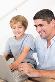 Father reaching son to use laptop — Stock Photo