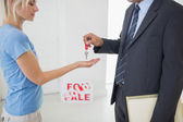 Real estate agent passing key to woman — Stock Photo