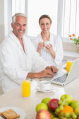 Smiling couple using laptop at breakfast in bathrobes — Stock Photo