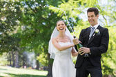 Newlywed couple popping cork of champagne — ストック写真
