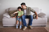 Father and son with football watching tv — Stock Photo