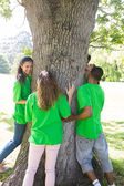 Environmentalists standing around tree — Stock Photo