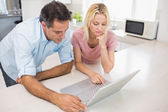 Concentrated couple using laptop — Stock Photo