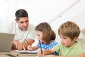 Father with laptop assisting children drawing — Stock Photo