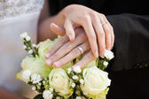 Newlywed couple with wedding rings and bouquet — Stockfoto