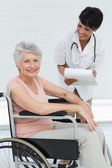Female doctor talking to a senior patient in wheelchair — Stock Photo