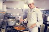 Cook preparing food in kitchen — Stock Photo
