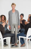 Rehab group applauding delighted woman standing up — Foto Stock